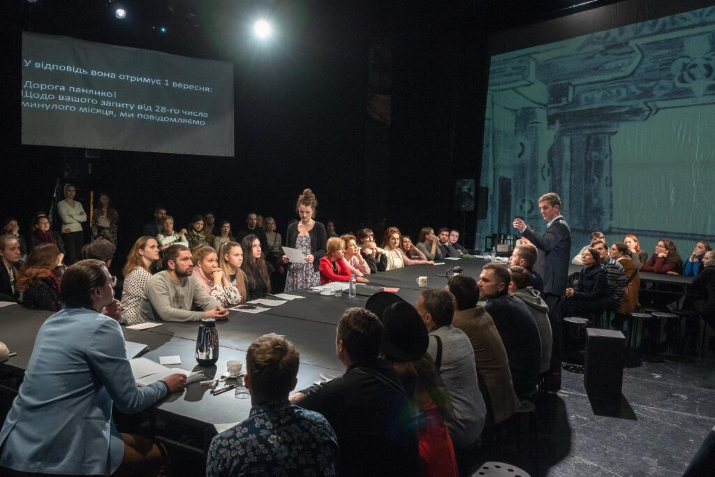 Artists and audience intermingle at a performance of <em>Solpersteine Staatstheater</em>, directed by Hans-Werner Kroesinger and Regine Dura, at the Kyiv Academic Molodyy Theatre, December 2018. (Photo credit: Oleksii Tovpyha)