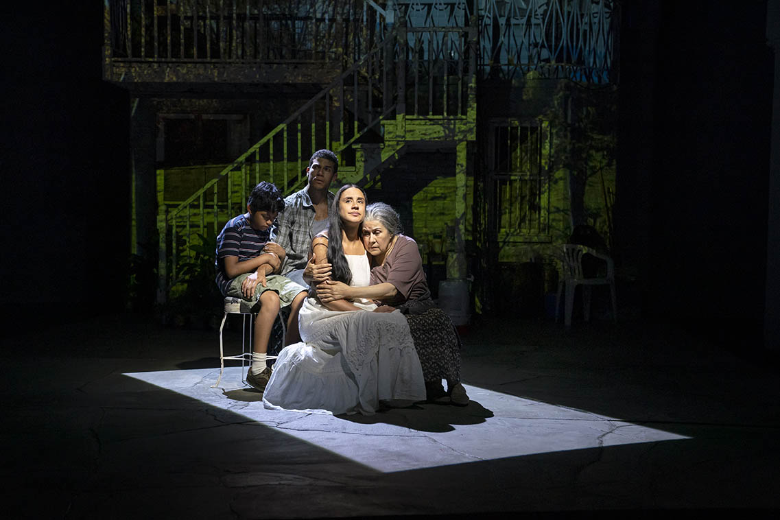 "Medea (Sabina Zuniga Varela), Tita (Socorro Santiago), Acan (Benjamin Luis McCracken), and Jason (Alex Hernandez) huddle together in the production of ""Mojada"""