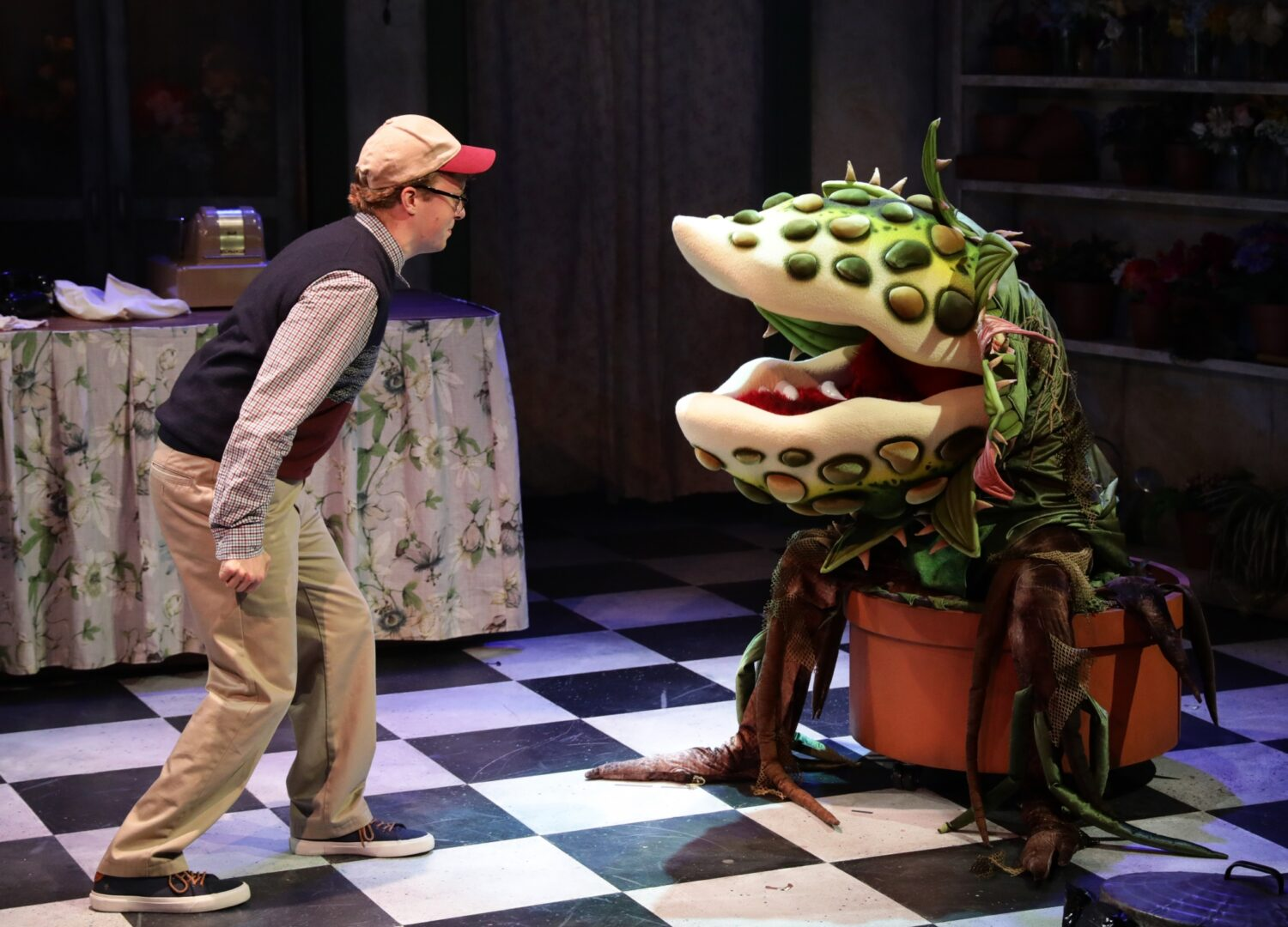 "Seymour and Audrey II face off in the Lyric Stage Company of Boston's production of ""Little Shop of Horrors"""