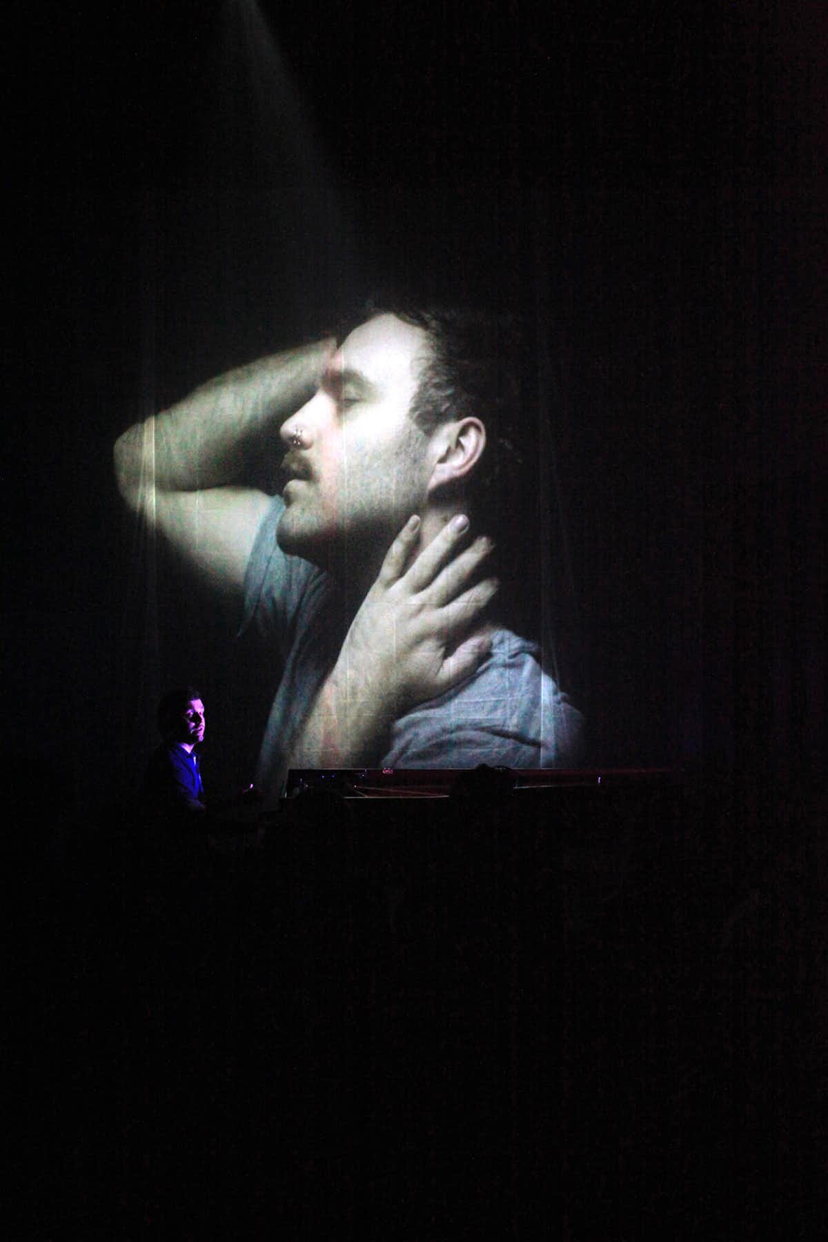 Dan Thorpe playing piano in front of a projected image of a man.