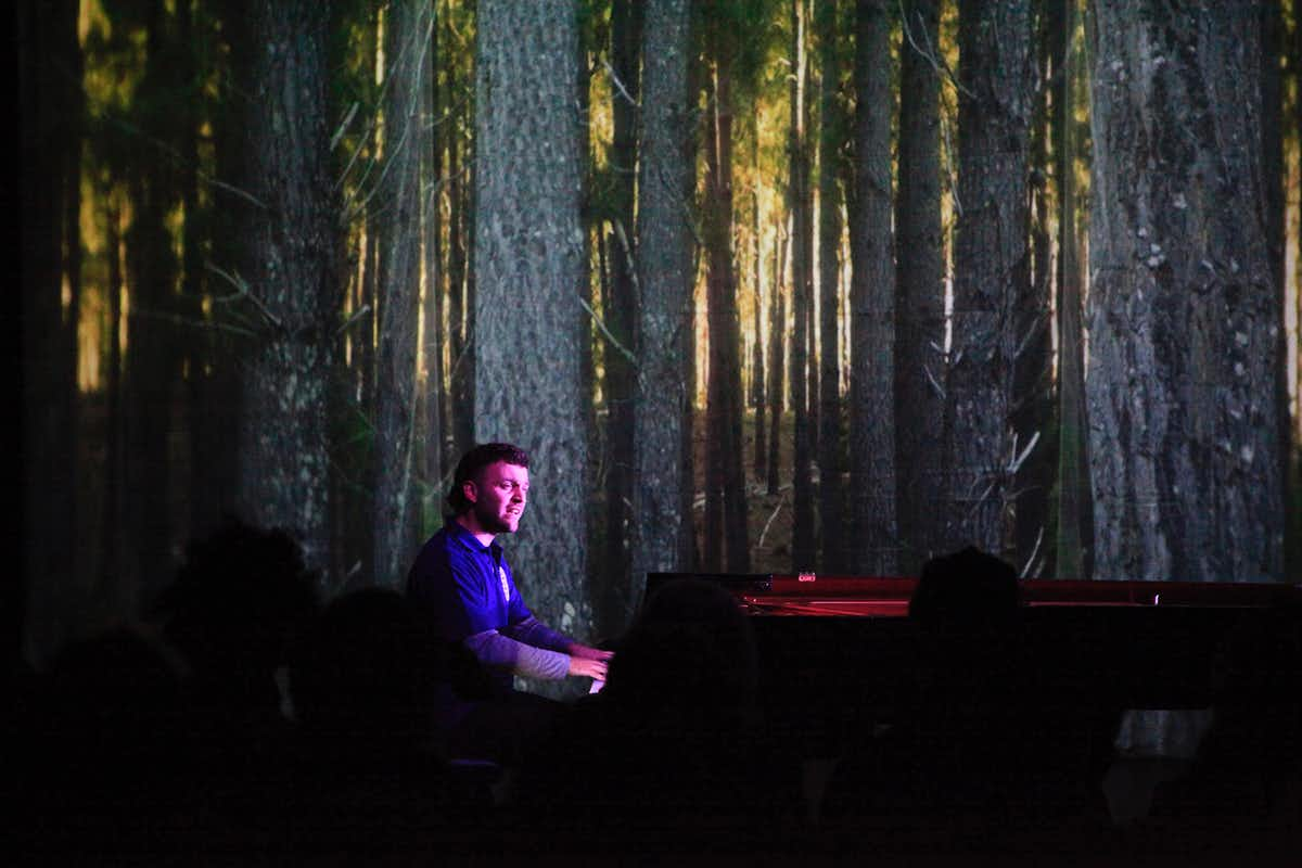 Dan Thorpe playing piano in front of a projected image of a forest.