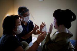 A photo of a geisha being prepared for a show.
