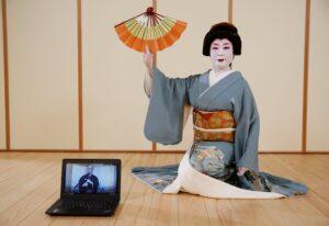 A geisha sits, holding a fan upside down.