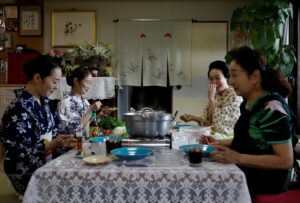 Japanese women sit around a dinner table