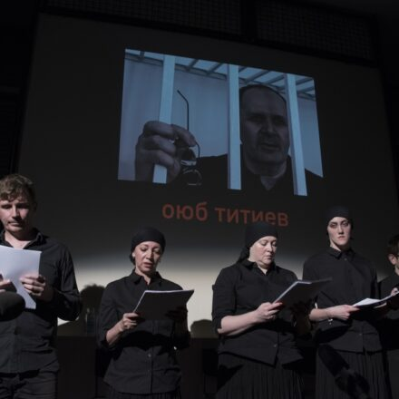 Five actors, all in black, stand in front of a projected image of a man who is behind bars. The name Oyub Titiev appears in red beneath his image.