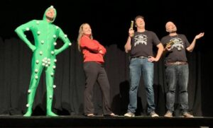 Against the black backdrop, four actors of the 2019 fringe San-Diego production of Space Force! stand on a stage. One is wearing a light green attire designed for filming actors for the CGI, others are wearing casual informal clothing.
