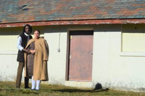 Outdoors photograph of two black actors, Brionna Bonet and Stephen Sampson, standing in from of a barn. The actors are wearing modernized historical clothing as their costumes for The Toby Gilmore Story.