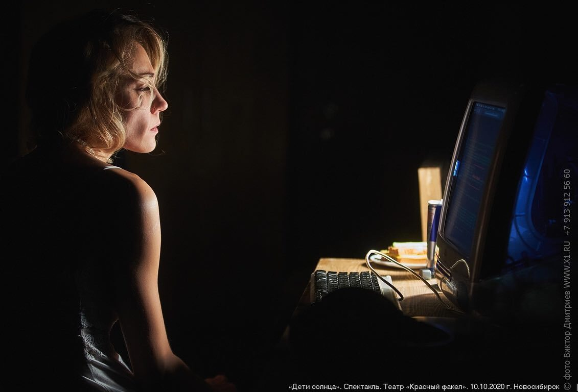 Photo of a caucasian actress seating in the dim light, profile facing a desk with a computer monitor on it.